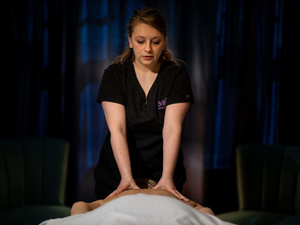 massage therapist massaging a customer's back.