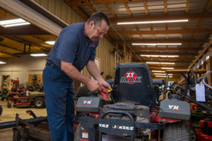 mechanic checking the oil of a riding lawnmower inside the repair shop