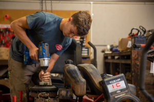 Man using a power tool on a riding lawn mower inside the repair shop