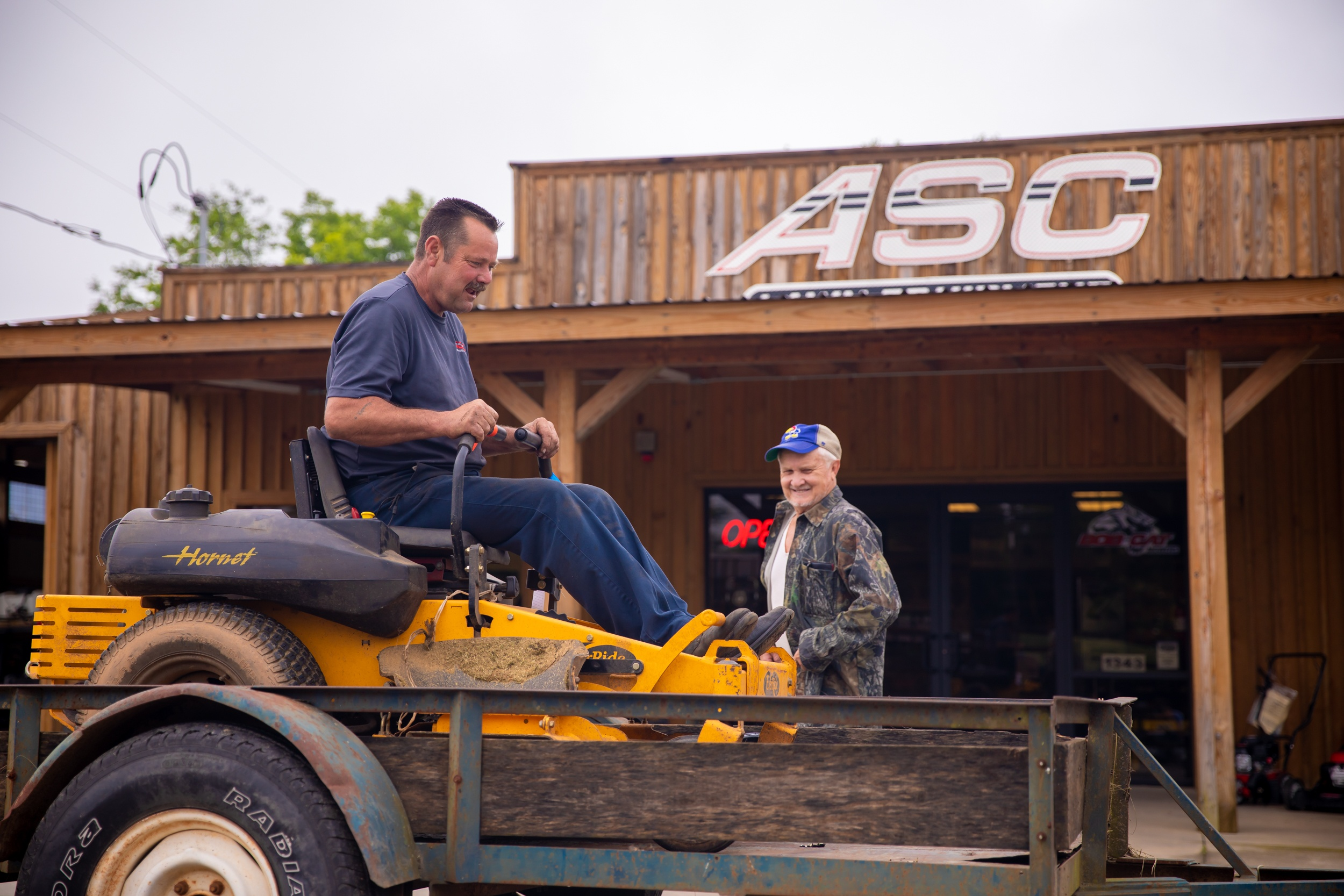 person driving a commercial lawn mower onto a trailer while another man looks on in front of the ASC Lawn Equipment building