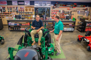 man sitting in a commercial lawn mower talking to a salesperson inside the store.